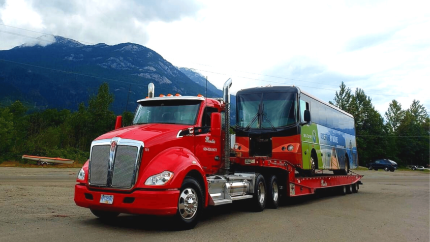 visual image of Mundie's truck towing a semi-bus